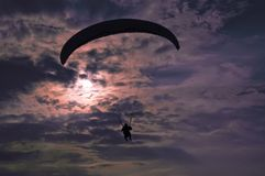 Extreme flying - paragliding at evening. Against the sun Royalty Free Stock Photography