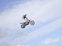 Extreme FMX stunt rider. An FMX rider pulls a stunt high in the air against a blue sky with clouds Stock Images