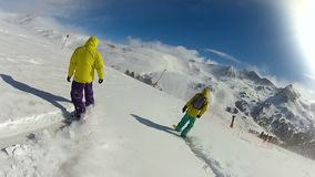Extreme friends riding snowboards down snowy mountain slope, active leisure stock video footage