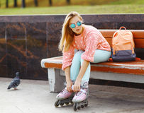Extreme, fun, youth and people concept - pretty stylish blonde. Girl in sunglasses with roller skates in the city park, cool roller girl outdoors stock photos