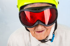 Extreme grannie. Funny grandma wearing a yellow bicycle helmet and ski  goggles Stock Image