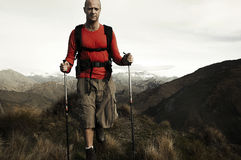 Extreme Hiking Across Rugged Mountains Concept. A man extreme hiking across rugged mountains Stock Image