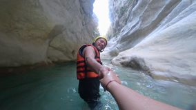Extreme honeymoon, young happy male tourist in protective clothes holding hand and leading his wife along water in cave. Among the stones stock video footage