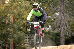 Extreme jump on a bike in forest. During competition downhill Royalty Free Stock Images