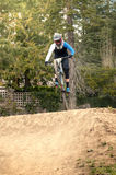 Extreme jump on a bike in forest. During competition downhill Royalty Free Stock Image