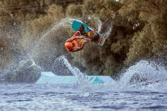 Extreme jump on wakeboarding. Man makes an extreme jump on wakeboarding, around there are a lot of splashes and splashes of water. This is an extreme sport Royalty Free Stock Photography