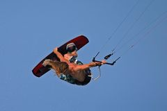 Extreme kiteboard grab. Radical kite-boarding action high in the sky Stock Photos