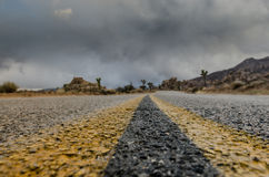 Extreme Low Angle of Desert Road on Stormy Day Stock Photos