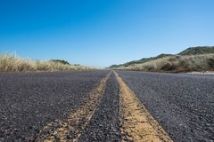 Extreme Low Angle of Road with Grasses. Over sand dunes Stock Image