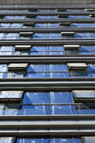 Diminishing Curtain Wall. Extreme low angle shot of an office building, with all its dusty windows open Stock Image