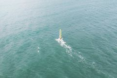 Extreme man athlete swims on the wind surf on the sea wave against the blue sea and the horizon. Extreme water sports. movement of. The red sail on the water stock photos