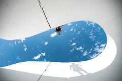 Extreme man with big shadow silhouette preparing for the jump over the gap between concrete walls Royalty Free Stock Photography