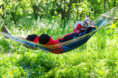 The extreme man rests in a hammock in a helmet and protects the. Body. An extreme kind of sport, a motocross rests in the woods after the competition Stock Images