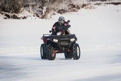 extreme Moto-ruiter in toestel op ATV in de winter in de sneeuw stock foto's