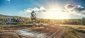 Extreme Motocross MX Rider riding on dirt track. On a sunny late summer day on public training session in preparation for Motocross event Stock Photo