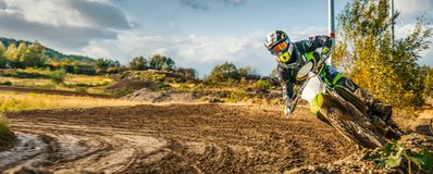 Extreme Motocross MX Rider riding on dirt track. On a sunny late summer day on public training session in preparation for Motocross event stock image