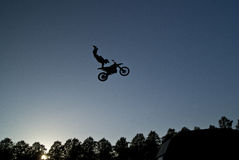 Motorcycle stunt rider in midair. Silhouetted motorcycle jump rider in mid air high over trees with blue sky background Stock Photography