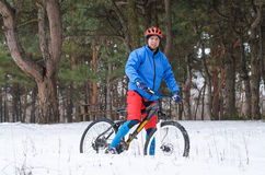 Extreme mountain biking in the snow-covered forest. Royalty Free Stock Photos