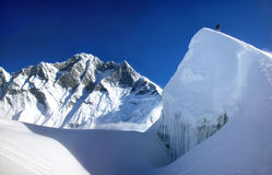 Extreme mountain climbing in Himalaya, Asia. Mountaineer on mountaintop near Lhotse as seen in the background. Taken in the Himalayas, Asia stock photos