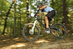 Extreme MTB cyclist. Mountain bike racer off road driving in forest Stock Images