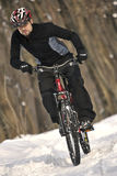 Extreme MTB cyclist. Mountain bike racer off road driving in snow covered forest Royalty Free Stock Photography