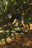 Extreme MTB cyclist. Mountain bike racer off road driving in forest Royalty Free Stock Photo
