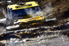 Extreme off-road car in mud crossing. Dirty yellow car in mud crossing Stock Photos
