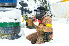 Extreme paintball player aiming behind tyres on snow Royalty Free Stock Images