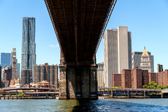 Extreme Perspective of the Brooklyn Bridge and the East River. The underside of the Brooklyn Bridge as seen from the Brooklyn side of the East River. As a Royalty Free Stock Photography