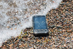 Extreme phone. Black waterproof, dustproof, shockproof mobile phone with touchscreen display lies on the beach sand Royalty Free Stock Photos