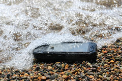 Extreme phone. Black waterproof, dustproof, shockproof mobile phone with touchscreen display lies on the beach sand Royalty Free Stock Images