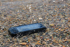 Extreme phone. Black waterproof, dustproof, shockproof mobile phone with touchscreen display lies on the beach sand covered with water Stock Photography
