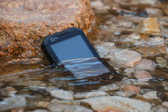 Extreme phone. Black waterproof, dustproof, shockproof mobile phone with touchscreen display stands in the water Stock Photos