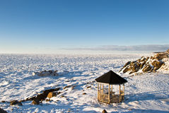 Extreme Picnic. Gazebo and Picnic Table on Coastline during Winter with View of Ice Pack to Horizon Royalty Free Stock Photo