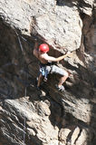Extreme Rock Climber. A rock climber works his way up a rock face protected by a rope clipped into bolts. He is wearing a helmet and quickdraws dangle from his Royalty Free Stock Photos