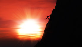 Extreme rock climber against a sunset sky Stock Images