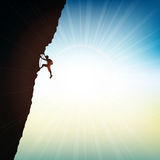 Extreme rock climber. Silhouette of an extreme rock climber against a sunny sky Stock Photography