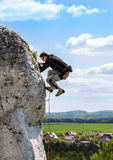 Extreme rock climbing, man on natural wall with blue sky. Stock Photography