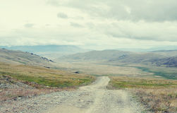 Extreme rocky road path down to a mountain valley from the pass Royalty Free Stock Photo