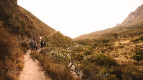 Extreme rocky terrain in mountains with hikers. Walking through dirt pathway. Group of young people walking through mountain trail stock images