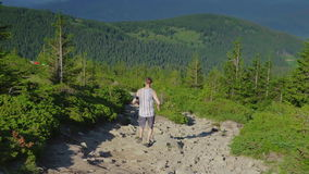 Extreme runner. A young man runs down the rocks along a steep mountain path. Steadicam shot stock footage