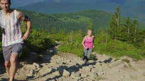 Extreme running. A woman with a personal trainer runs up a steep mountain path in the mountains. stock footage