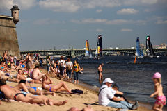 Extreme Sailing Series in St. Petersburg, Russia. St. Petersburg, Russia - August 21, 2015: People on the beach watching races of Extreme 40 catamarans during St stock images