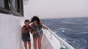 Extreme shot of mom and son on the ship in a storm. Woman and a little boy walk on a pleasure boat during a strong wind and huge waves hovering on the ship stock video footage