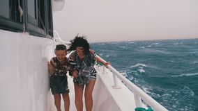 Extreme Shot of Mom and Son on the Ship in a Storm. Woman and a little boy walk on a pleasure boat during a strong wind and huge waves hovering on the ship stock footage