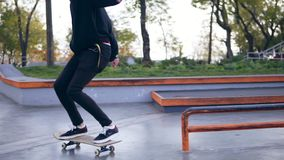 Extreme skateboarder listening to the music in earphones grinding down rail in the skatepark. Slowmotion shot stock footage