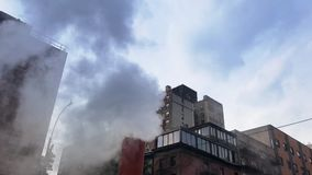 Slow Motion View of Smoke Pipe on Manhattan Street. An extreme slow motion view of smoke venting from a pipe on a Manhattan street with buildings in the stock video footage
