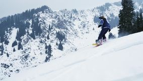 Extreme snowboarder woman riding by powder at mountain backcountry. Snowboarding, winter activities stock video
