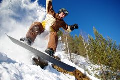 Extreme snowboarding. Snowboarder jumping through air with deep blue sky in background Royalty Free Stock Images