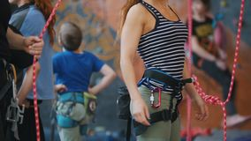 Extreme sport, bouldering. Trainer helps the woman to put on the protection ropes. Mid shot stock video footage